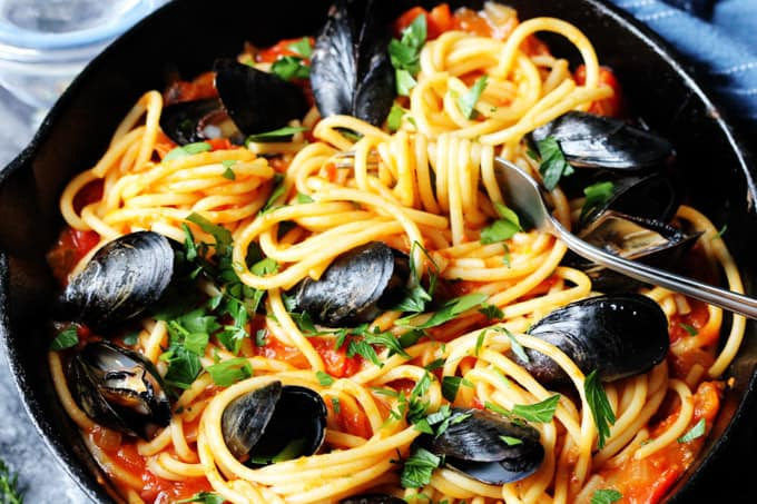Horizontal photo of pasta with mussels and spicy tomato sauce in a skillet