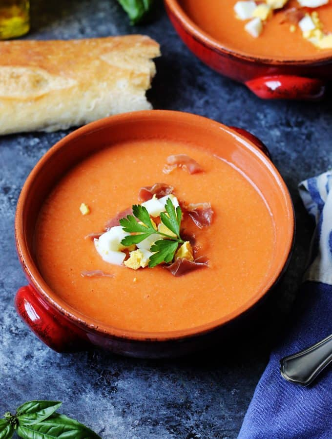 Salmorejo in bowls with ham and egg on top and bread on a side