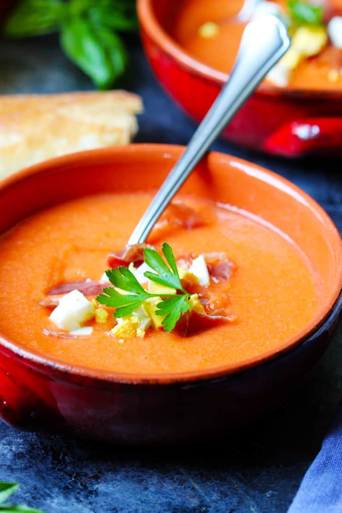 Close up shot of Salmorejo soup in orange bowl with spoon.