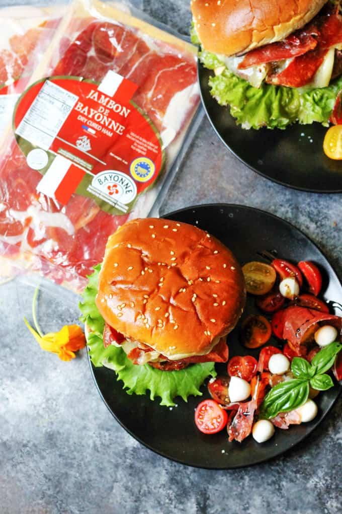 Turkey burgers on black plates with side caprese salad and Bayonne ham on a side