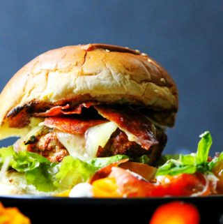 Turkey burger with Bayonne Ham with side salad on a plate