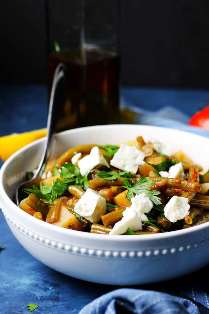 Greek Green Beans in a white bowl with feta