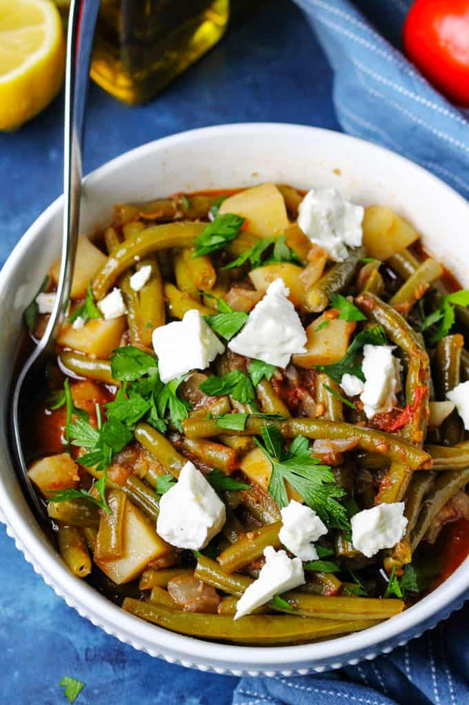 Fasolakia in a white bowl with spoon and feta on top