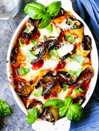 Eggplant Rollatini Parmigiana in a casserole dish with towel on a side