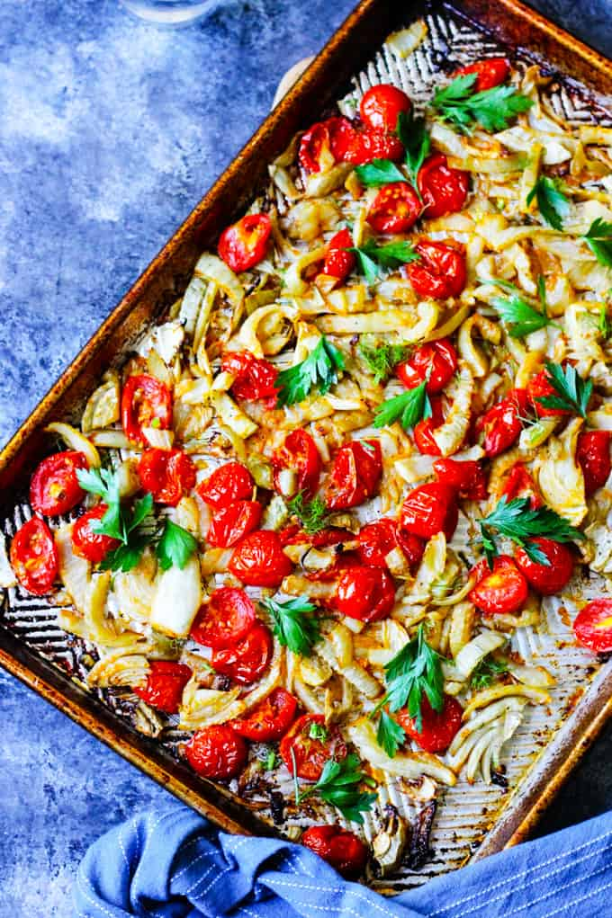 Roasted fennel and cherry tomatoes on a baking sheet with blue background