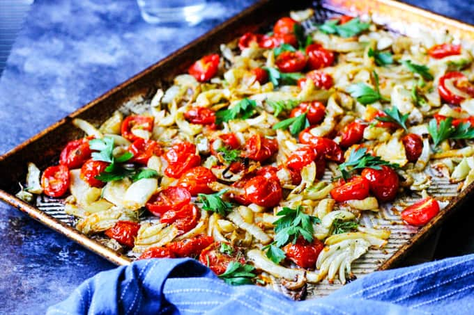 Roasted fennel with tomatoes on a cookie sheet