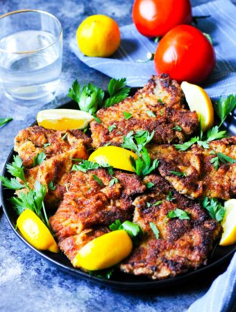 Veal Milanese on a plate with lemon wedges