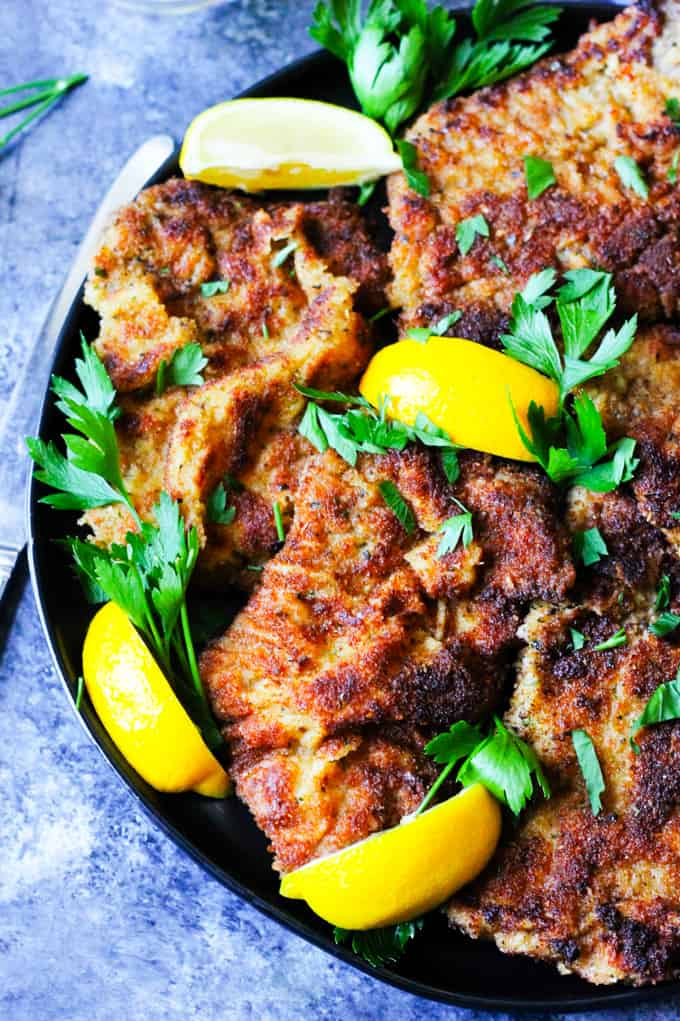 Breaded veal cutlets on a black plate with lemon pieces