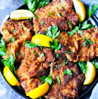Italian breaded veal cutlets on a plate with blue background