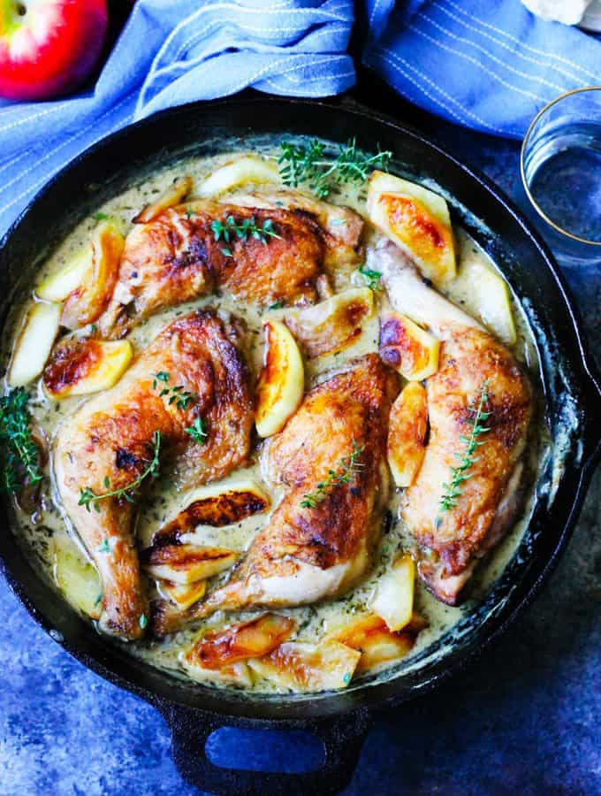 Chicken Normandy braised in apple cider and cream in a skillet with apples