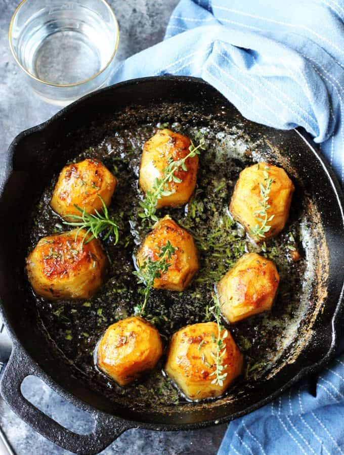 Fondant Potatoes in cast iron skillet with herbs