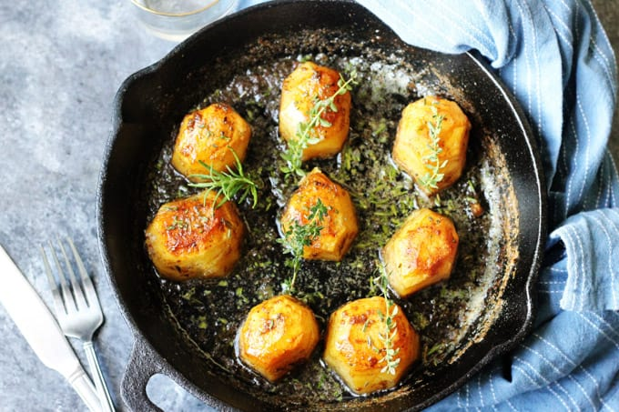 Horizontal Photo of Fondant potatoes in a cast iron sklllet