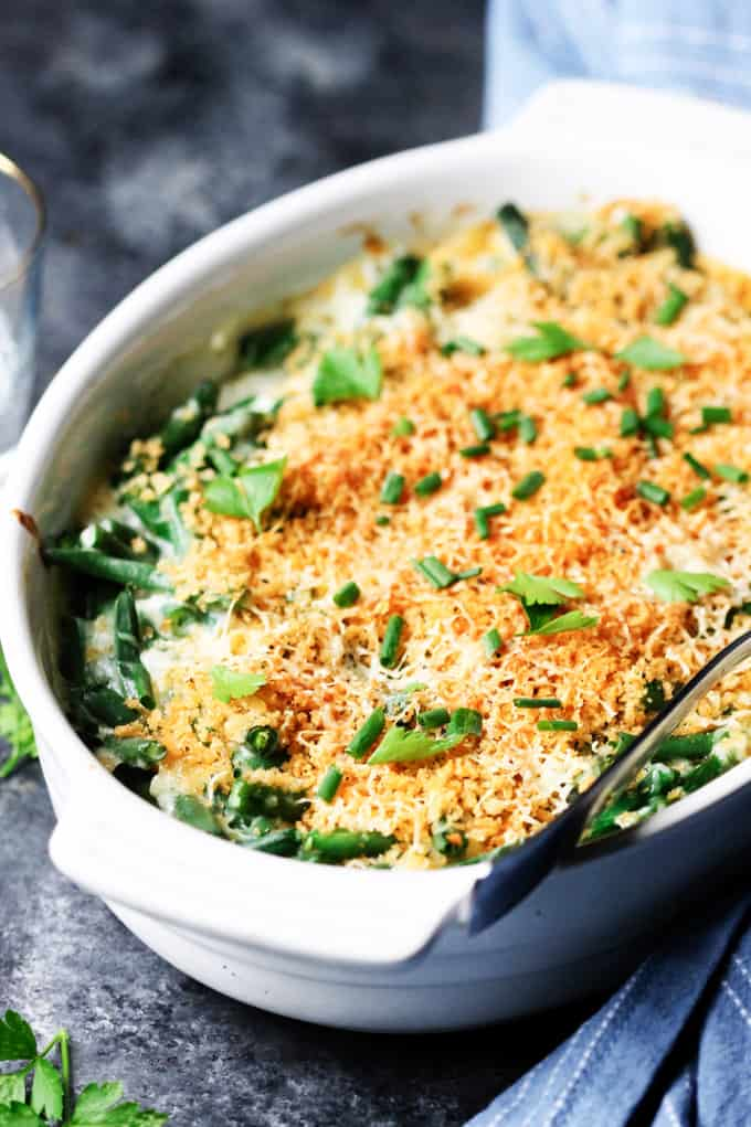 Green bean casserole in a white dish with spoon