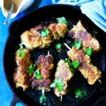 Breaded pork on skewers in cast iron pan