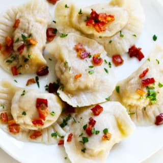 Polish Meat Pierogi on a white plate with bacon bits