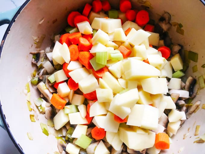 carrots, onions and potatoes added to a pot of mushrooms and onions