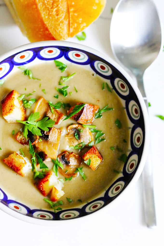 Creamy mushroom soup with croutons in a blue bowl